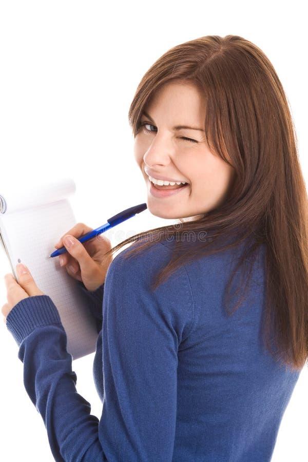 A mulher bonita faz registros pela pena no bloco de notas fotos de stock