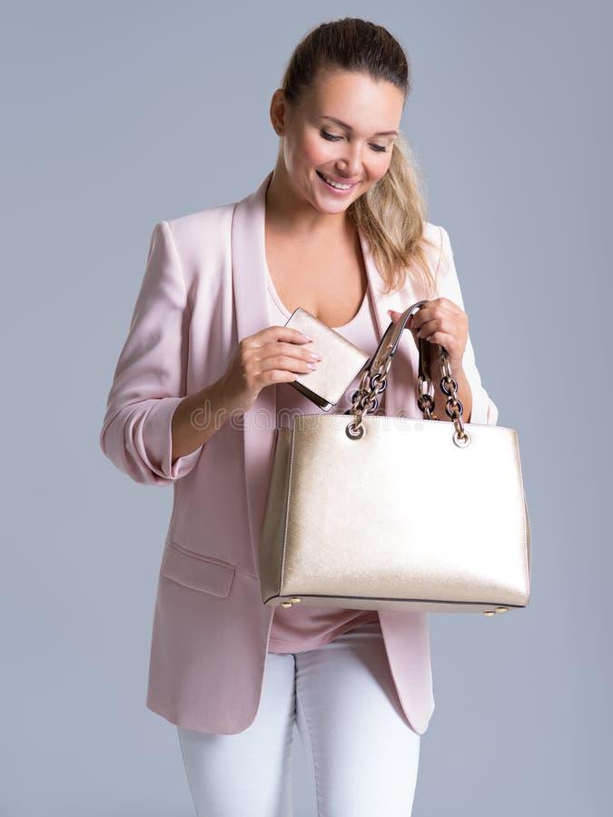 Mulher bonita feliz com bolsa e carteira na compra fotos de stock