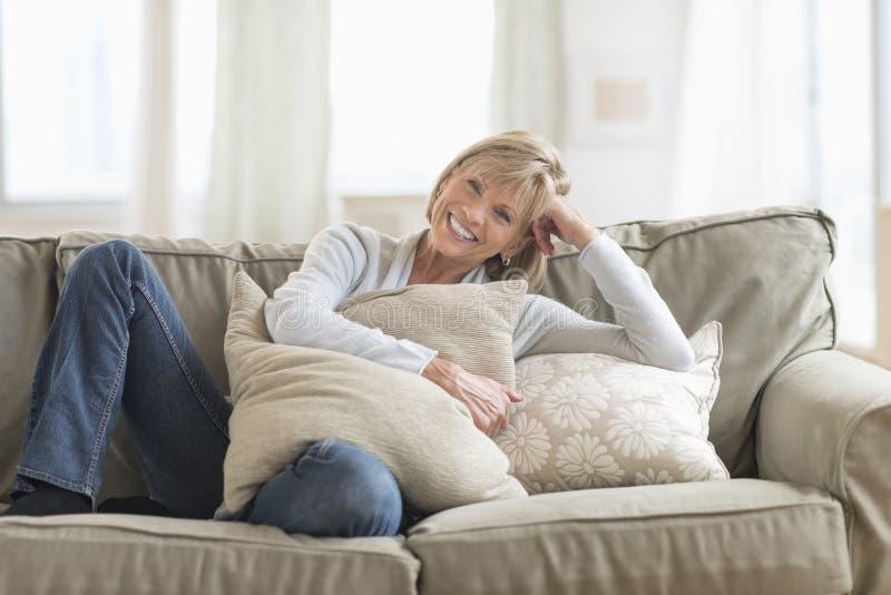 Mulher bonita feliz com os coxins que relaxam no sofá fotografia de stock