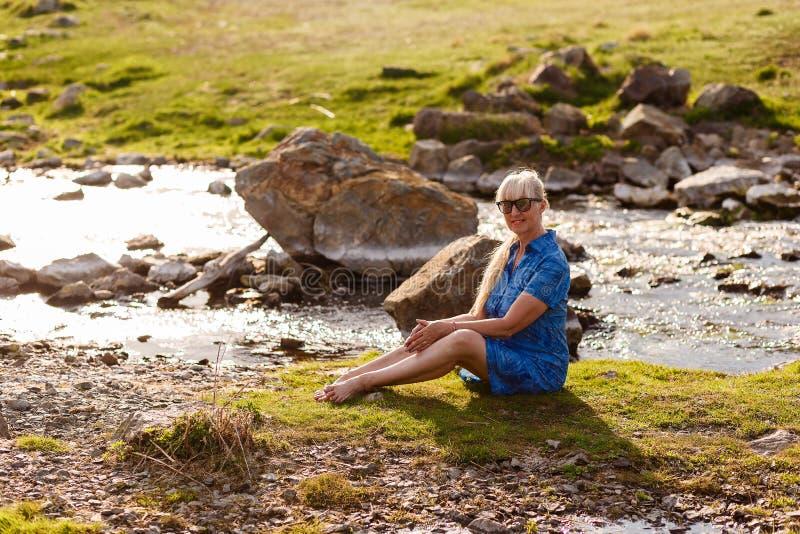 Mulher bonita feliz da idade da reforma no vestido azul que senta-se na grama perto do rio foto de stock