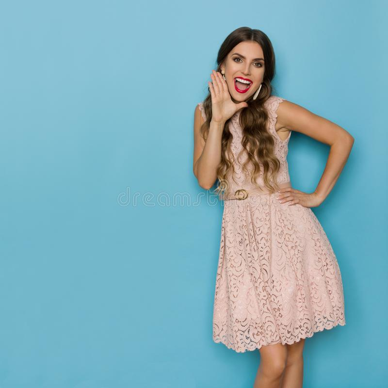Mulher bonita feliz no laço bege Mini Dress Is Holding Hand em Chin And Shouting foto de stock