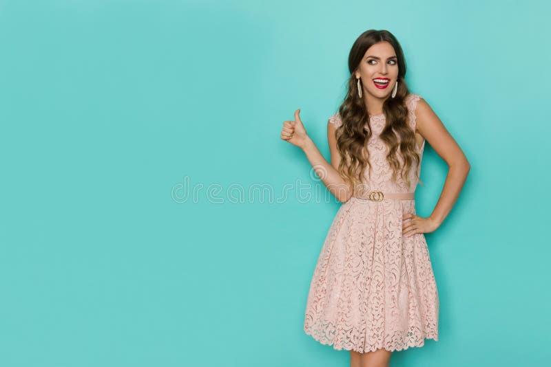 Mulher bonita feliz no laço bege Mini Dress Is Showing Thumb acima e fala foto de stock