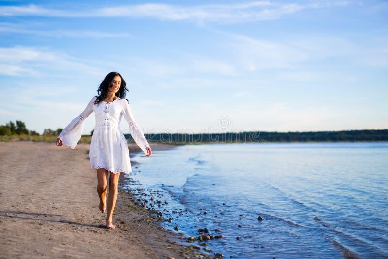Mulher bonita feliz no vestido branco que anda na praia fotos de stock