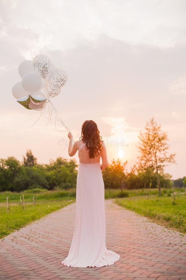 Mulher bonita feliz no vestido longo cor-de-rosa que anda com os balões de ar no parque verde no dia de verão do nascer do sol imagens de stock royalty free