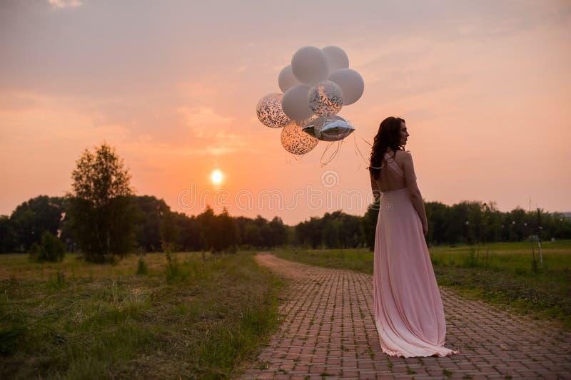 Mulher bonita feliz no vestido longo cor-de-rosa que anda com os balões de ar no parque verde no dia de verão do nascer do sol imagens de stock
