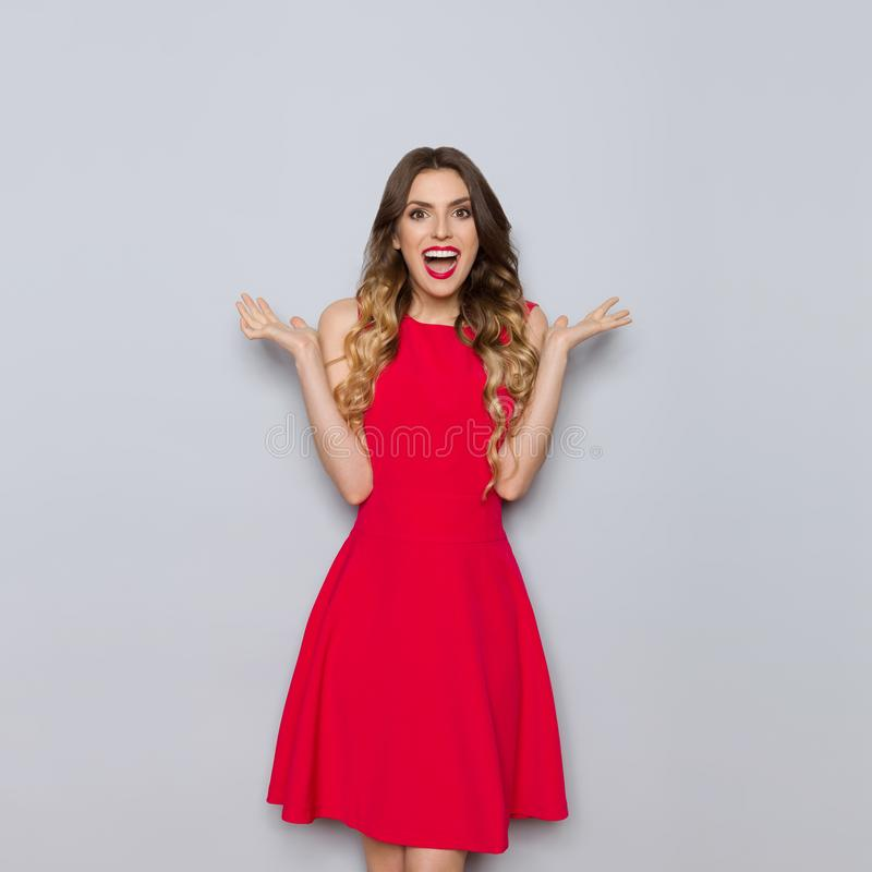 A mulher bonita feliz no vestido vermelho é gritaria e gesticular fotos de stock