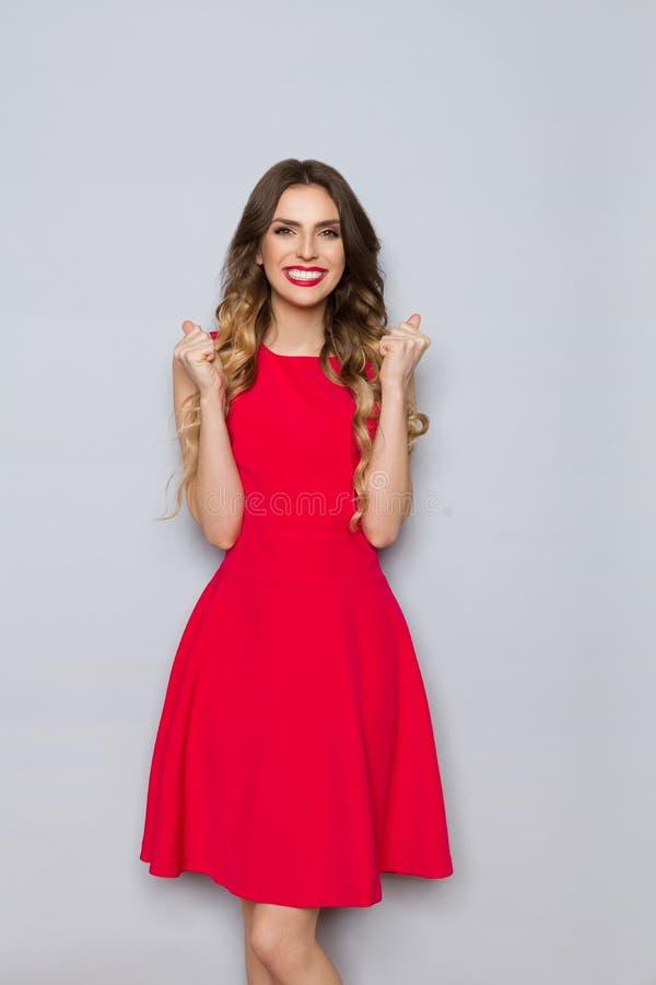 A mulher bonita feliz no vestido vermelho está sorrindo e punho de aperto imagens de stock royalty free