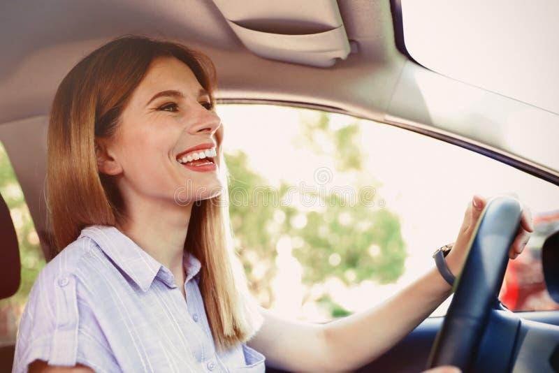 Mulher bonita feliz que conduz o carro foto de stock