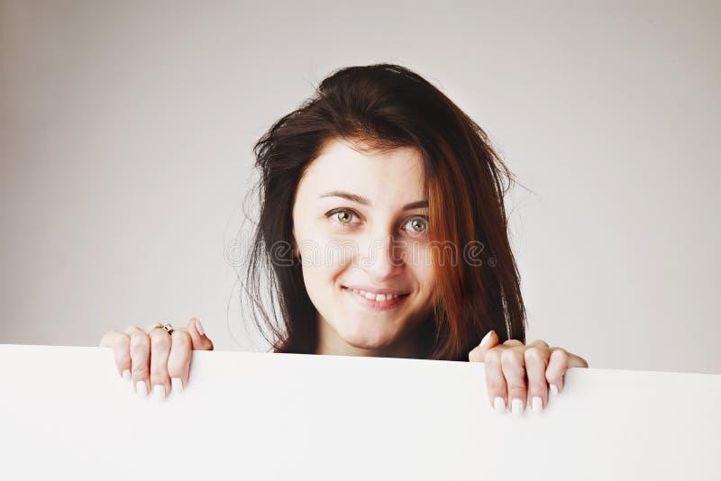 Mulher bonita feliz que espreita atrás de um whiteboard fotos de stock royalty free