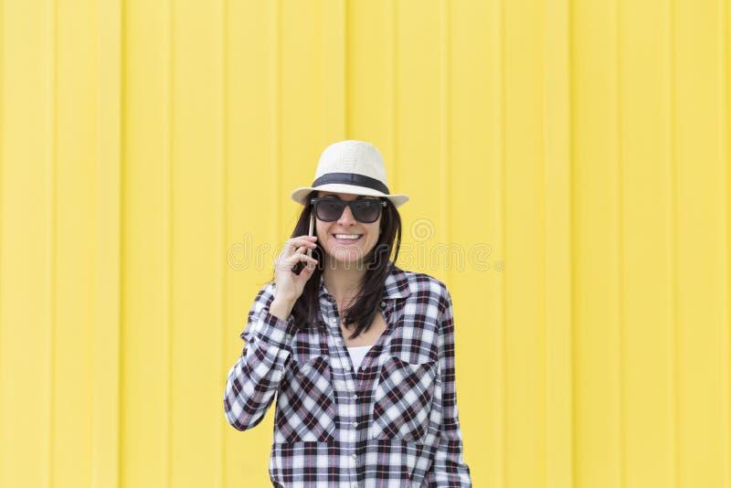 Mulher bonita feliz que fala no telefone sobre o backgroun amarelo imagem de stock royalty free