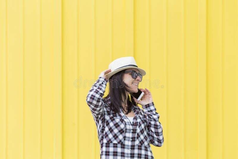 Mulher bonita feliz que fala no telefone sobre o backgroun amarelo foto de stock royalty free