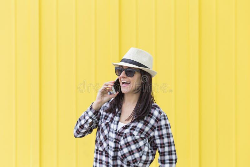 Mulher bonita feliz que fala no telefone sobre o backgroun amarelo imagem de stock