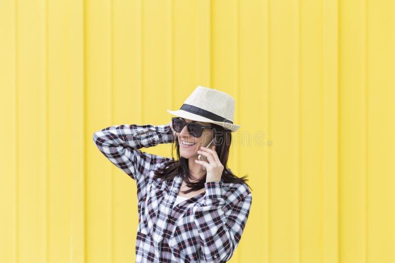 Mulher bonita feliz que fala no telefone sobre o backgroun amarelo foto de stock