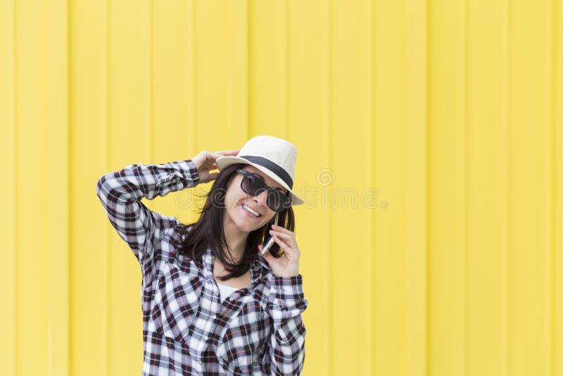 Mulher bonita feliz que fala no telefone sobre o backgroun amarelo imagens de stock