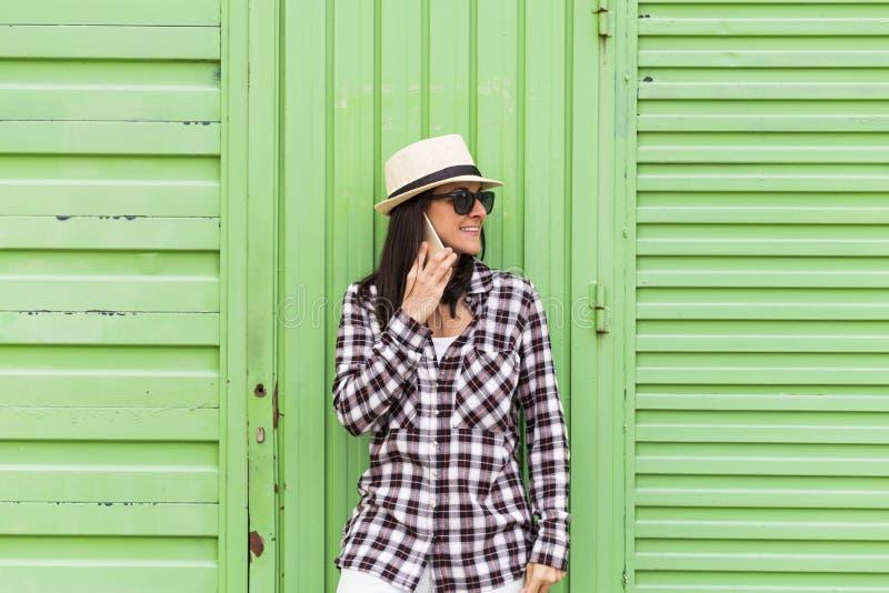 Mulher bonita feliz que fala no telefone sobre o fundo verde fotos de stock