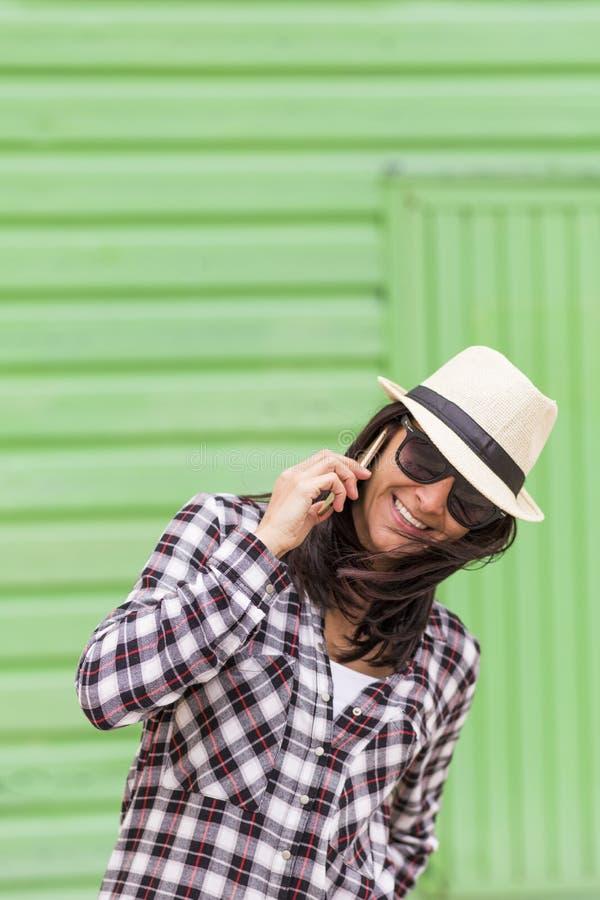 Mulher bonita feliz que fala no telefone sobre o fundo verde fotografia de stock royalty free