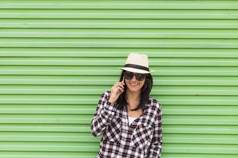 Mulher bonita feliz que fala no telefone sobre o fundo verde foto de stock
