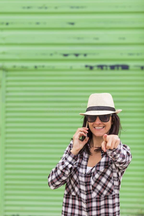 Mulher bonita feliz que fala no telefone sobre o fundo verde imagens de stock royalty free
