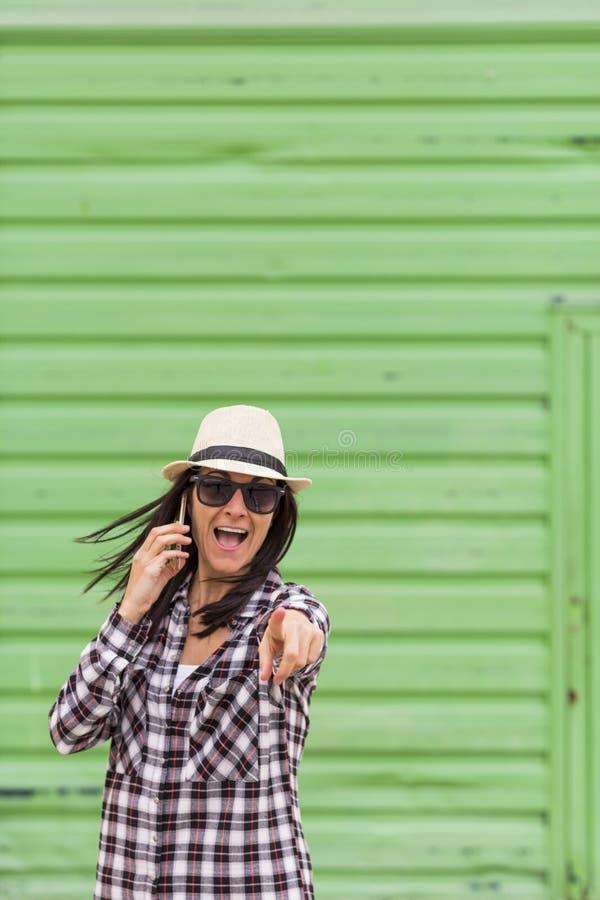 Mulher bonita feliz que fala no telefone sobre o fundo verde imagem de stock