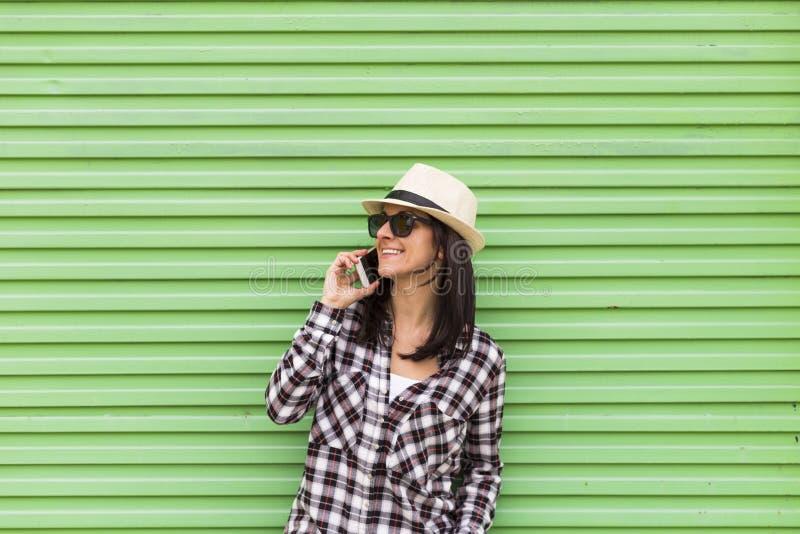 Mulher bonita feliz que fala no telefone sobre o fundo verde imagens de stock