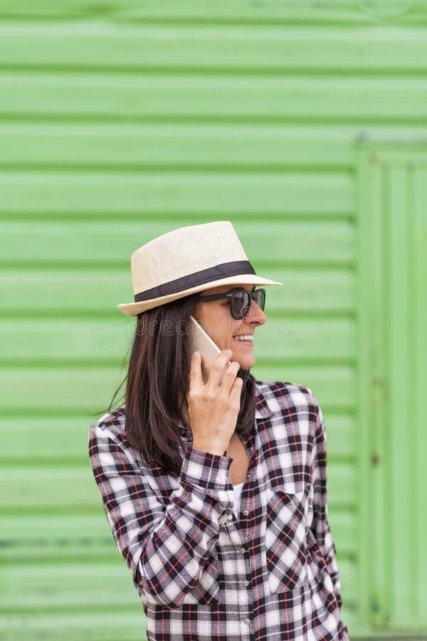 Mulher bonita feliz que fala no telefone sobre o fundo verde foto de stock royalty free