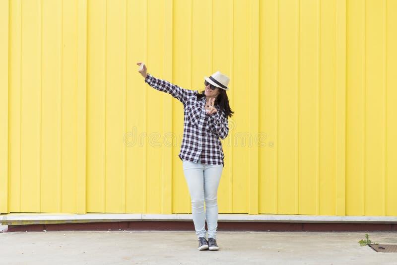 Mulher bonita feliz que fala um selfie com um ove da câmera do vintage imagens de stock