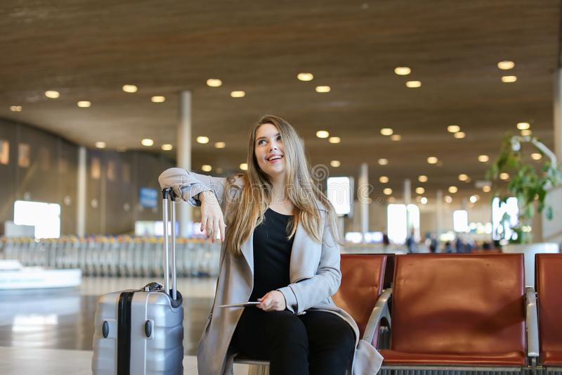 Mulher bonita feliz que senta-se na sala de espera do aeroporto com tabuleta e valise cinzento imagens de stock royalty free