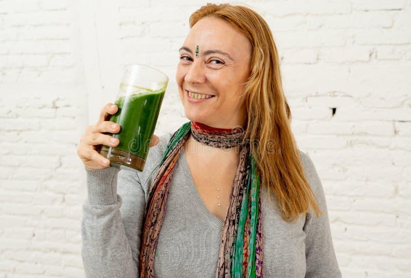 Mulher bonita feliz que sorri e que bebe o batido saudável do legume fresco no estilo de vida saudável fotografia de stock royalty free
