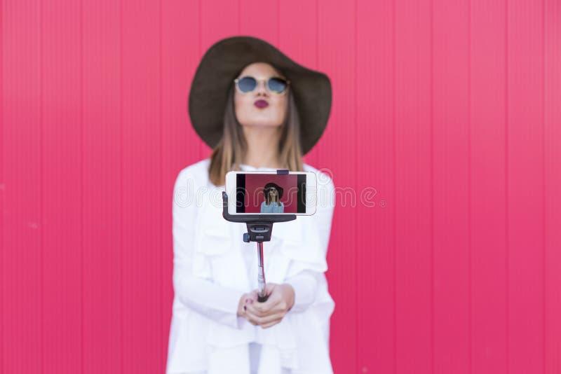 Mulher bonita feliz que toma um selfie com o smartphone sobre b vermelho imagem de stock royalty free