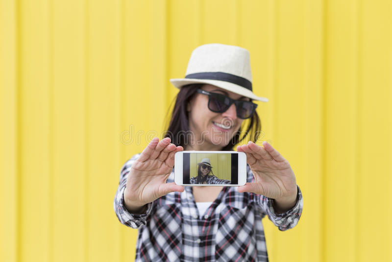 Mulher bonita feliz que toma um selfie com o smartphone sobre o yello foto de stock