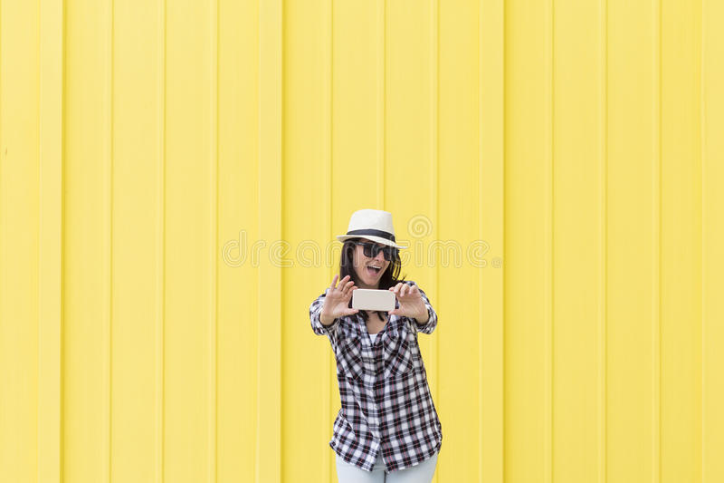 Mulher bonita feliz que toma um selfie com o smartphone sobre o yello imagem de stock royalty free