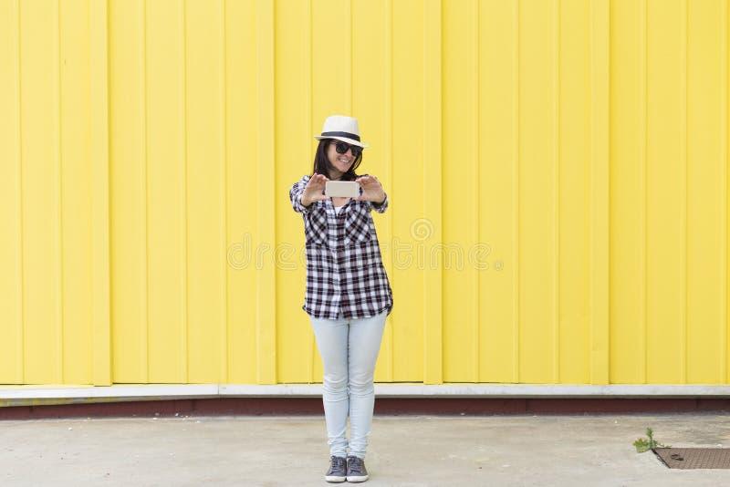 Mulher bonita feliz que toma um selfie com o smartphone sobre o yello fotos de stock