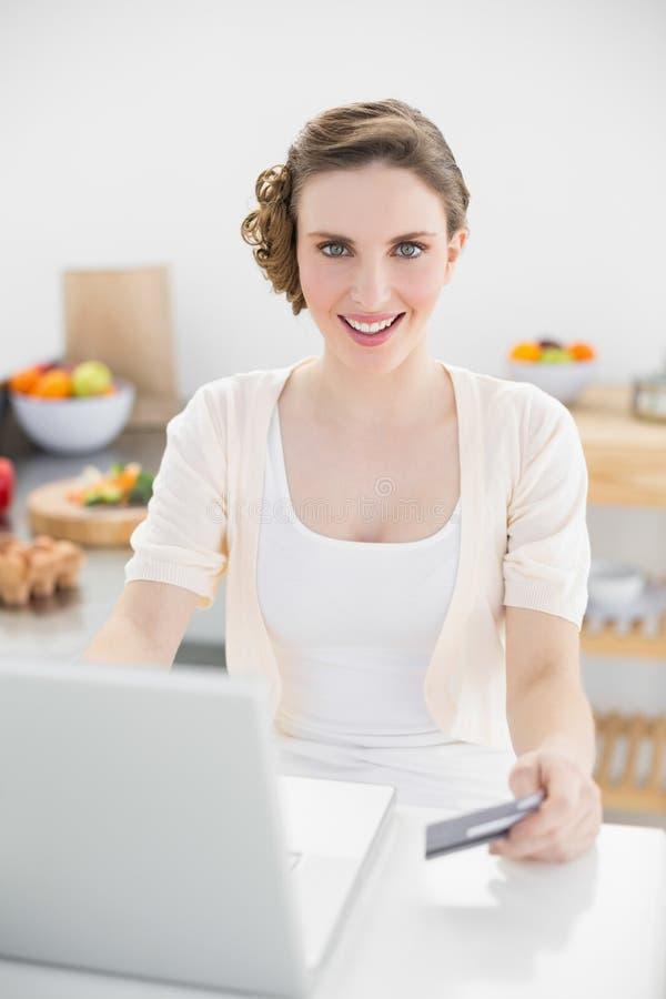 Mulher bonita feliz que usa seu caderno para as compras ao domicílio que sentam-se na cozinha imagens de stock royalty free