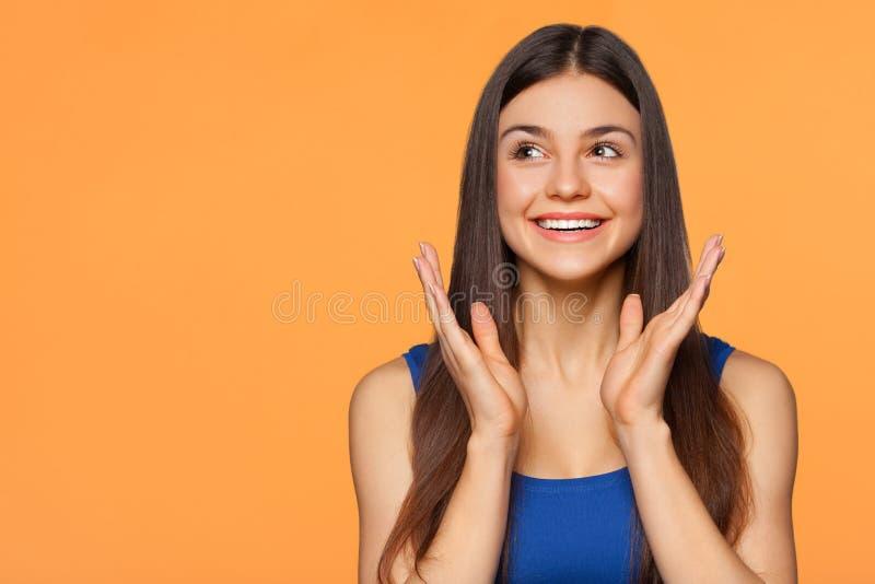 Mulher bonita feliz surpreendida que olha lateralmente no excitamento, isolado no fundo alaranjado fotos de stock royalty free