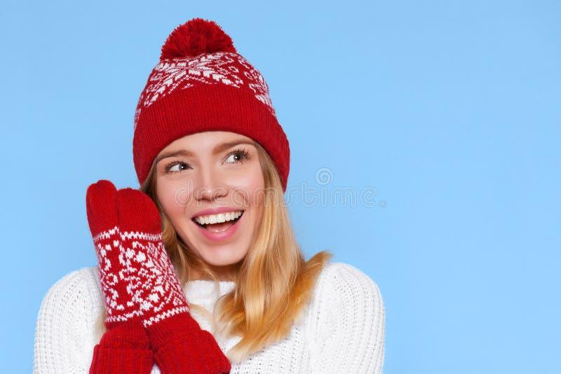 Mulher bonita feliz surpreendida que olha lateralmente no excitamento Menina do Natal que veste o chapéu e mitenes mornos feitos  imagem de stock