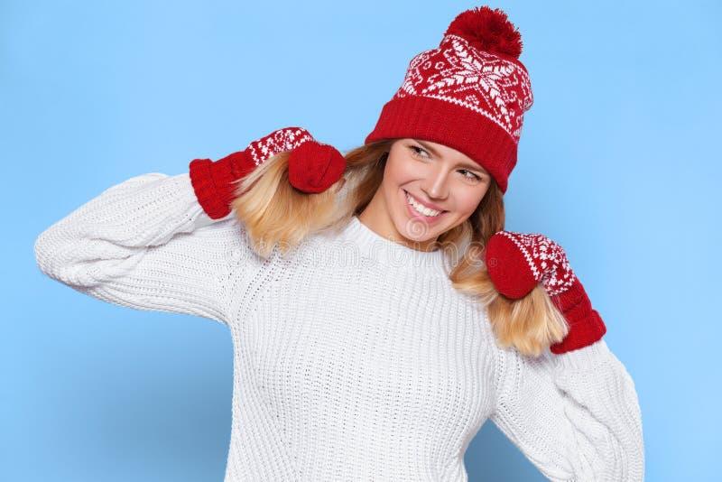 Mulher bonita feliz surpreendida que olha lateralmente no excitamento Menina do Natal que veste o chapéu e mitenes mornos feitos  imagem de stock royalty free