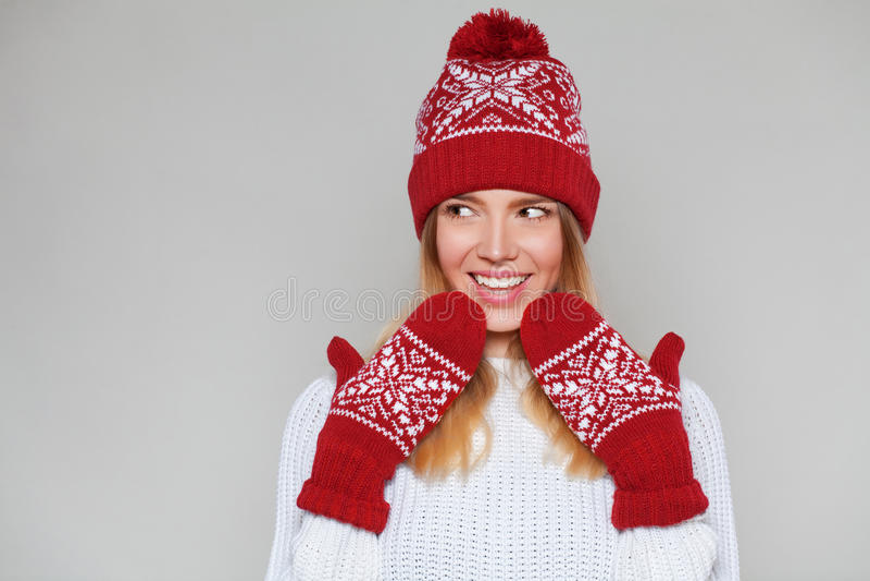 Mulher bonita feliz surpreendida que olha lateralmente no excitamento Menina do Natal que veste o chapéu feito malha e os mitenes imagem de stock royalty free