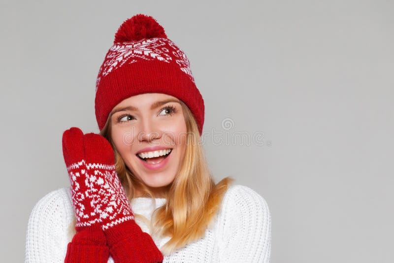 Mulher bonita feliz surpreendida que olha lateralmente no excitamento Menina do Natal que veste o chapéu feito malha e os mitenes foto de stock royalty free