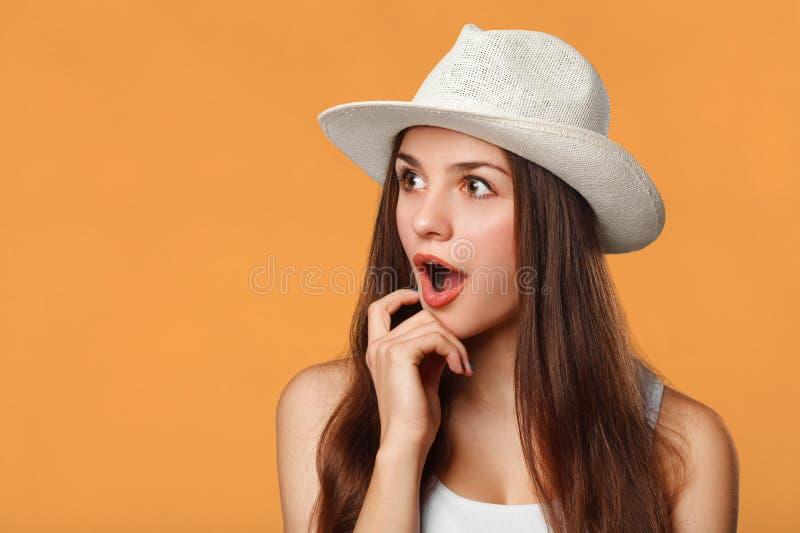 Mulher bonita feliz surpreendida que olha lateralmente nos excitemen, isolados no fundo alaranjado fotografia de stock royalty free