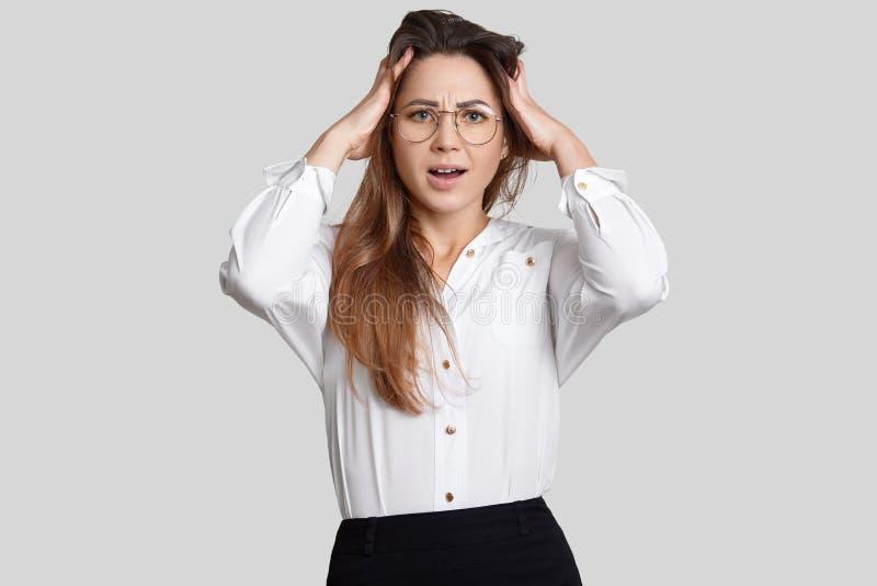 A mulher bonita forçada na roupa do escritório, mantém ambas as mãos na cabeça, tem o problema no trabalho, isolado sobre o fundo imagem de stock