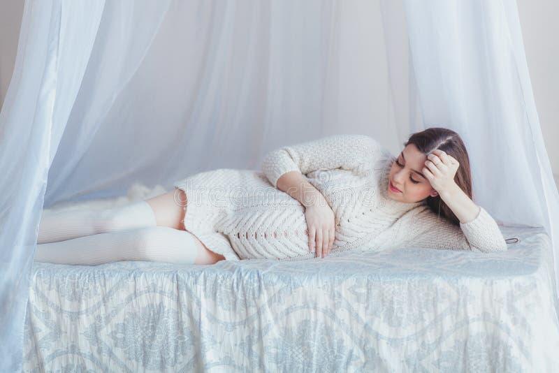 Mulher bonita grávida que encontra-se na cama do dossel Camiseta e meias feitas malha branco vestindo imagens de stock