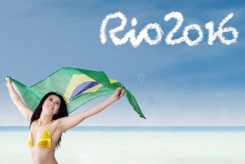 A mulher bonita guarda a bandeira brasileira na praia foto de stock
