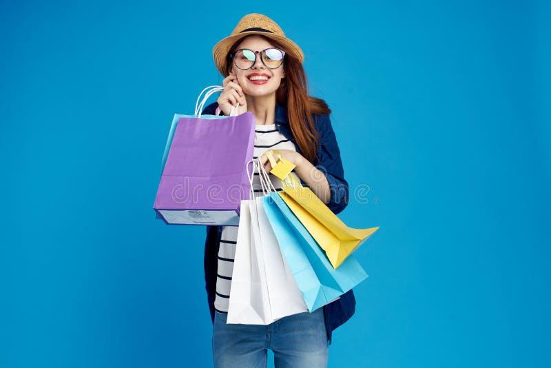 A mulher bonita guarda muitos pacotes em um fundo azul em um chapéu e em vidros, sorriso, compra, cliente, loja, shopaholic fotos de stock