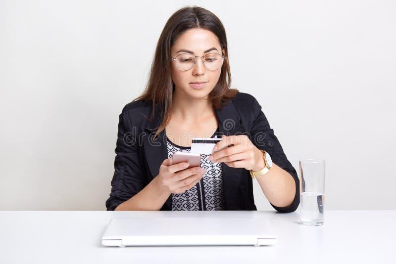 A mulher bonita guarda o cartão de crédito plástico, faz a verificação de dados da operação bancária, tem a compra em linha, usa  fotos de stock