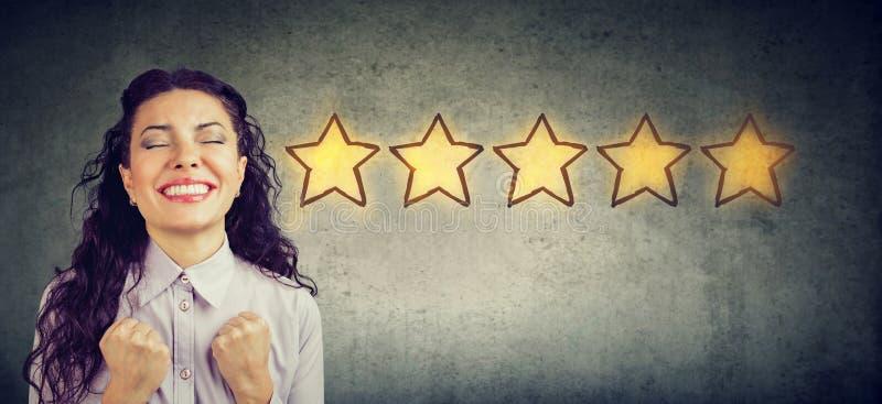 Mulher bonita heerful do ¡ de Ð que sorri comemorando cinco estrelas que avaliam para o serviço proporcionado imagens de stock royalty free