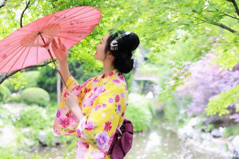 A mulher bonita japonesa asiática tradicional da gueixa veste a noiva do quimono com um guarda-chuva vermelho em um graden fotos de stock