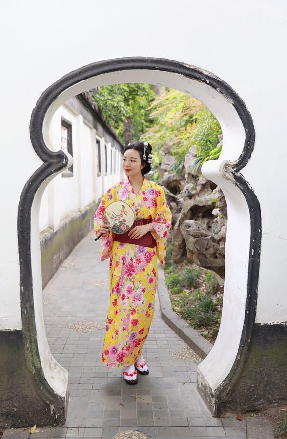 A mulher bonita japonesa asiática tradicional veste o quimono em um suporte do parque do jardim da mola pelo bambu aprecia o fã d imagem de stock royalty free