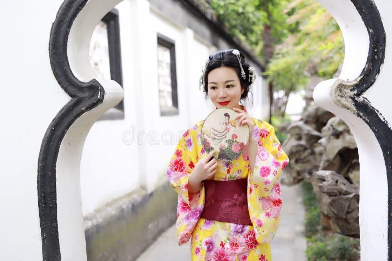 A mulher bonita japonesa asiática tradicional veste o quimono em um suporte do parque do jardim da mola pelo bambu aprecia o fã d fotos de stock royalty free