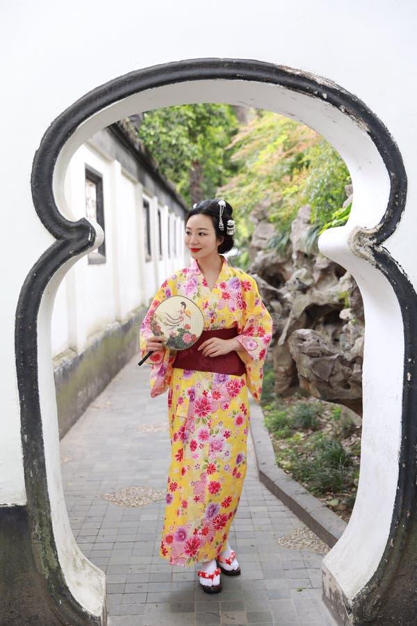 A mulher bonita japonesa asiática tradicional veste o quimono em um suporte do parque do jardim da mola pelo bambu aprecia o fã d imagem de stock