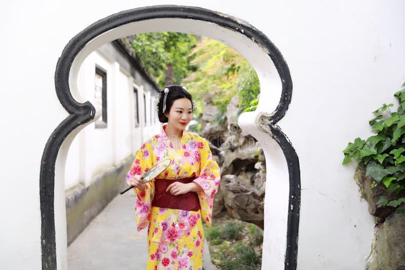 A mulher bonita japonesa asiática tradicional veste o quimono em um suporte do parque do jardim da mola pelo bambu aprecia o fã d fotografia de stock royalty free